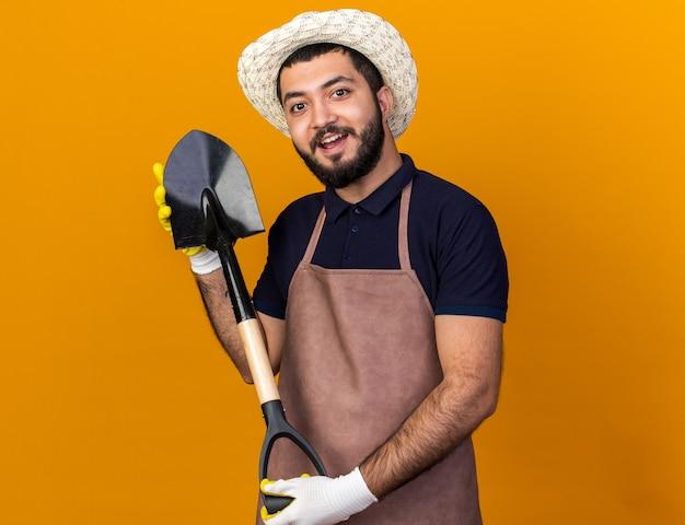 コピースペースでオレンジ色の壁に分離されたスペードを保持しているガーデニング帽子と手袋を身に着けている若い白人男性の庭師を驚かせた