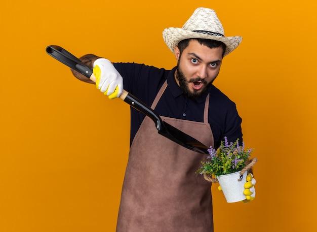 Sorpreso giovane maschio caucasico giardiniere che indossa cappello e guanti da giardinaggio tenendo la vanga su un vaso di fiori isolato sulla parete arancione con spazio di copia