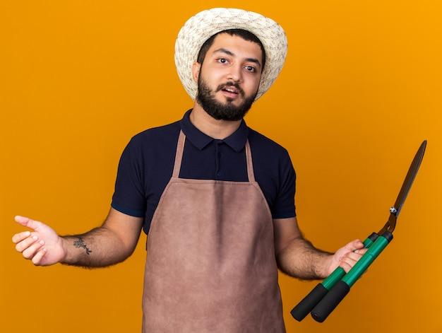 コピースペースとオレンジ色の壁に分離されたガーデニングはさみを保持しているガーデニング帽子をかぶって驚いた若い白人男性の庭師