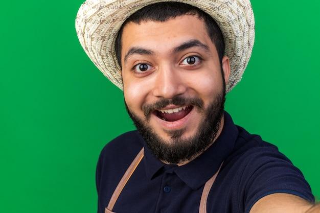 Sorpreso il giovane giardiniere maschio caucasico che indossa il cappello da giardinaggio tiene e guarda prendendo selfie isolato sulla parete verde con spazio di copia