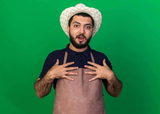 Surprised young caucasian male gardener wearing gardening hat puts hands on chest isolated on green wall with copy space