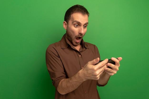 Удивленный молодой кавказский человек, держащий и смотрящий на мобильный телефон, изолированный на зеленом фоне с копией пространства
