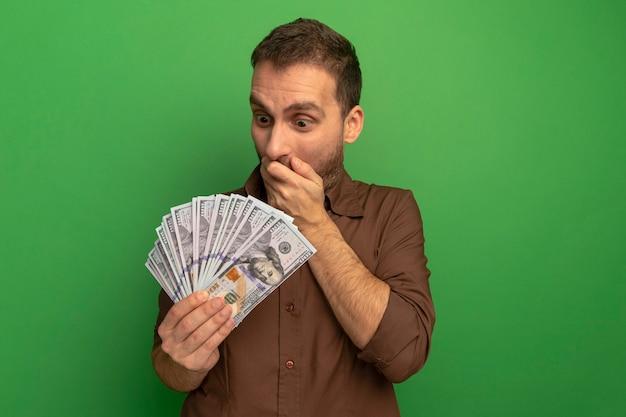 Giovane uomo caucasico sorpreso che tiene e che esamina soldi tenendo la mano sulla bocca isolata sulla parete verde con lo spazio della copia