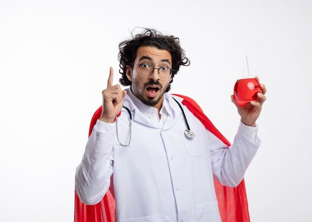 赤いマントと聴診器を首にかけた医者の制服を着た光学ガラスの驚いた若い白人男性は、ガラスフラスコに赤い化学液体を保持し、白い壁を指しています