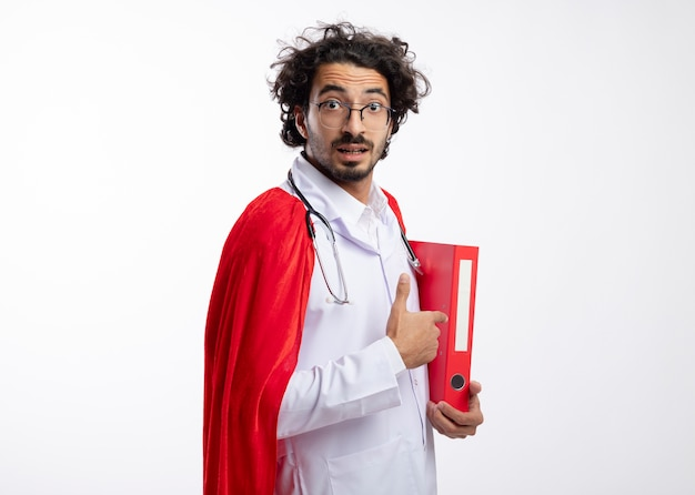 Удивленный молодой кавказец в оптических очках, одетый в медицинскую форму с красным плащом и со стетоскопом на шее, стоит боком, держа и указывая на папку с файлами с копией пространства