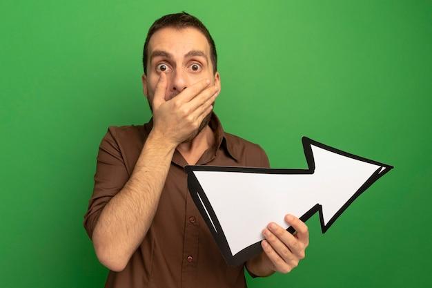 Giovane uomo caucasico sorpreso che guarda l'obbiettivo che tiene il segno della freccia che indica al lato che tiene la mano sulla bocca isolata su fondo verde