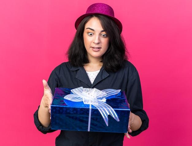분홍색 벽에 격리된 선물 꾸러미를 들고 파티 모자를 쓰고 놀란 젊은 백인 파티 소녀