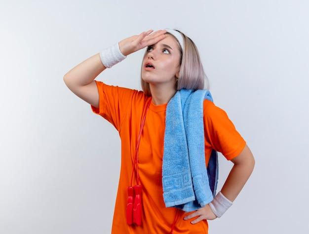 중괄호와 어깨에 수건을 들고 머리띠 팔찌를 착용 목 주위에 밧줄 점프 놀된 젊은 백인 스포티 한 소녀는 흰색 벽에 고립 된 찾고 이마에 손을 넣습니다