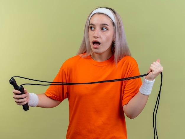 Удивленная молодая кавказская спортивная девушка с подтяжками, носящая повязку на голову и браслеты держит скакалку, глядя в сторону