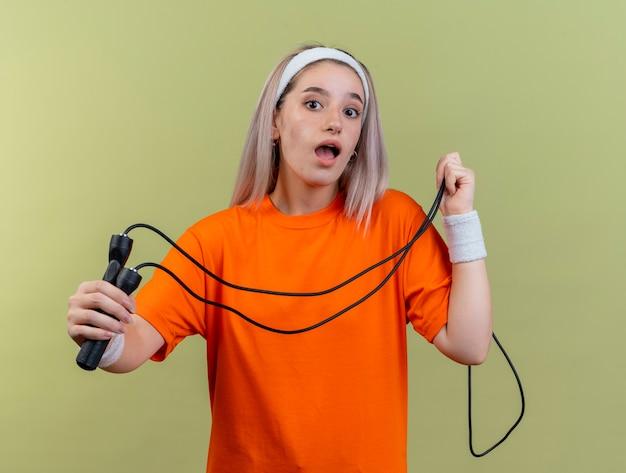 Удивленная молодая кавказская спортивная девушка с подтяжками, с повязкой на голову и браслетами держит скакалку