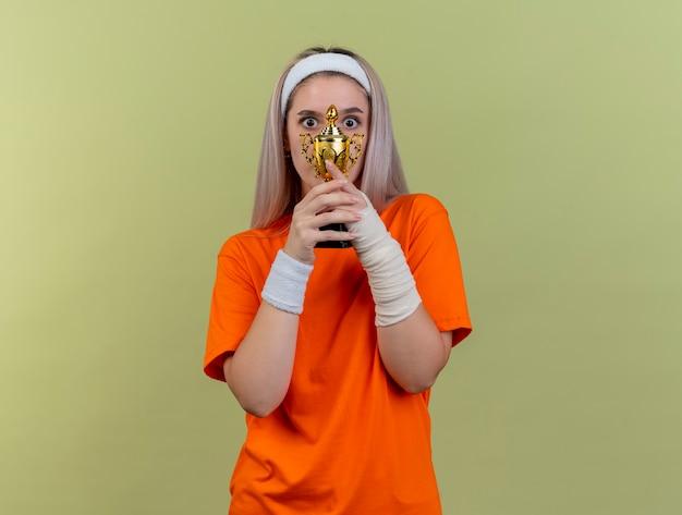 Удивленная молодая кавказская спортивная девушка с подтяжками, с повязкой на голову и браслетами держит кубок победителя