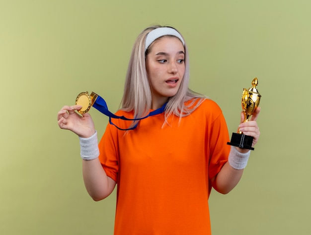 La giovane ragazza sportiva caucasica sorpresa con bretelle che indossa fascia e braccialetti tiene la medaglia d'oro e guarda la coppa del vincitore