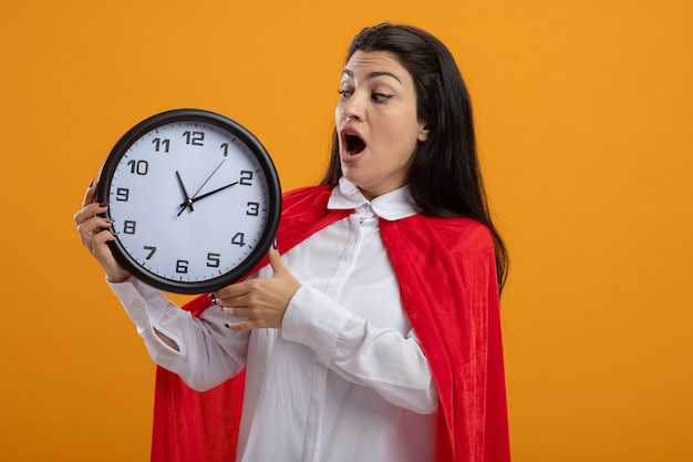 Ragazza giovane supereroe caucasica sorpresa che tiene e che esamina orologio isolato sulla parete arancione con lo spazio della copia