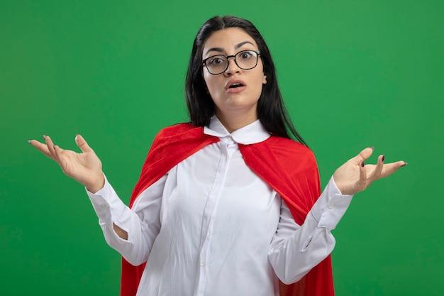 Ragazza giovane supereroe caucasica sorpresa con gli occhiali che mostra le mani vuote che guarda l'obbiettivo isolato su priorità bassa verde