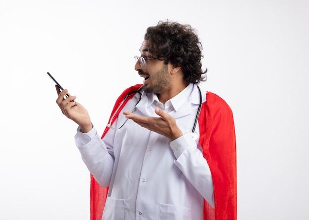 Sorpreso giovane caucasico supereroe uomo in occhiali ottici che indossa l'uniforme del medico con mantello rosso e con lo stetoscopio intorno al collo guarda e punta al telefono