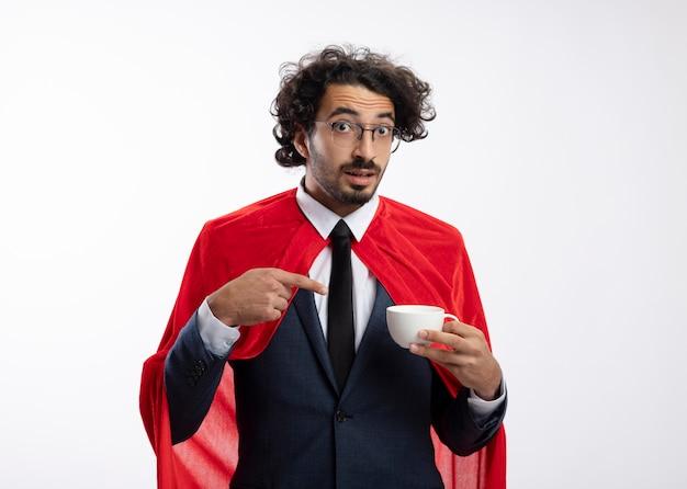 Sorpreso giovane supereroe caucasico con occhiali ottici che indossa un abito con mantello rosso tiene e punta alla tazza