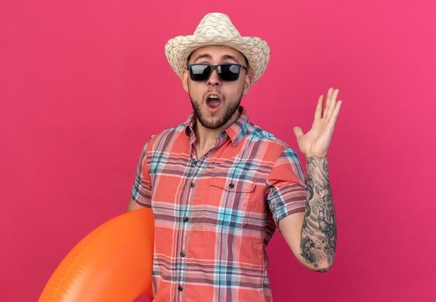 コピースペースでピンクの背景に分離された上げられた手で立っている浮き輪を保持しているサングラスでわらのビーチ帽子を持つ驚いた若い白人旅行者の男