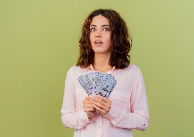 La giovane donna caucasica sorpresa tiene i soldi isolati su fondo verde con lo spazio della copia