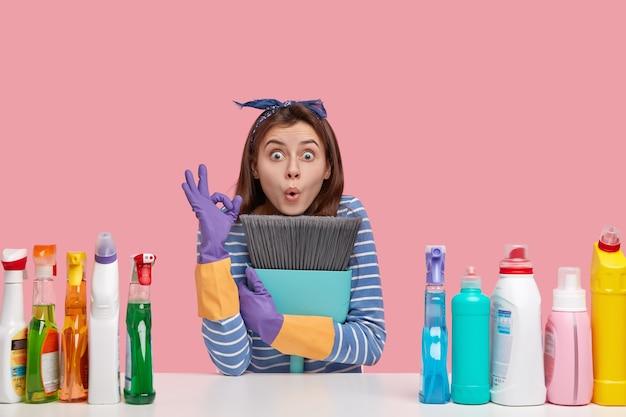 驚いた若い白人女性は大丈夫なジェスチャーをし、ほうきをしっかりと保ち、すべてが大丈夫であることを示し、床を掃除します