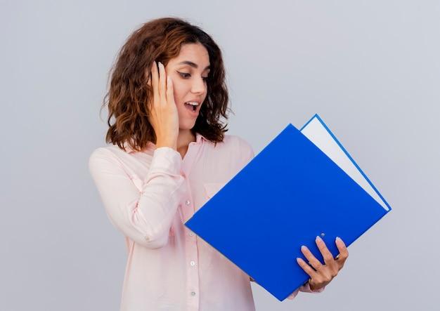 Удивленная молодая кавказская женщина кладет руку на лицо, держа и глядя на папку с файлами, изолированную на белом фоне с копией пространства