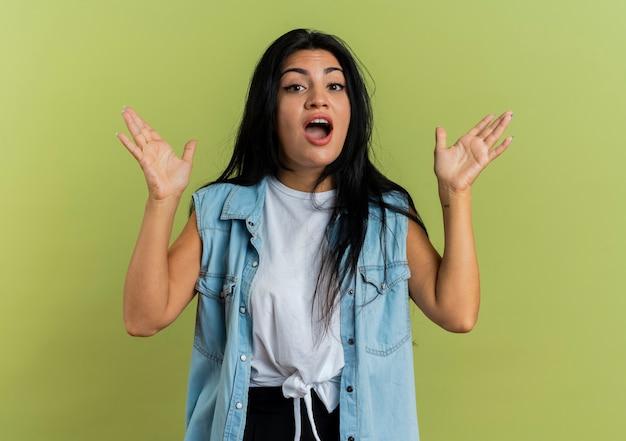 La giovane donna caucasica sorpresa sta con le mani alzate isolate su fondo verde oliva con lo spazio della copia
