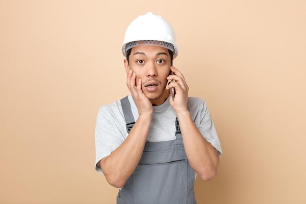 안전 헬멧을 착용하고 얼굴에 손을 유지하는 전화 통화 유니폼을 입고 놀란 젊은 건설 노동자