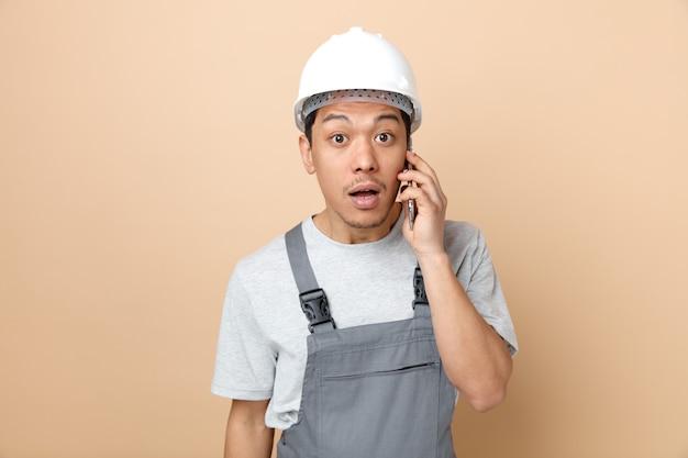 安全ヘルメットと制服を着て電話で話している驚いた若い建設労働者