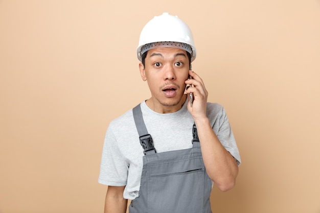 Giovane operaio edile sorpreso che indossa casco di sicurezza e uniforme che comunica sul telefono