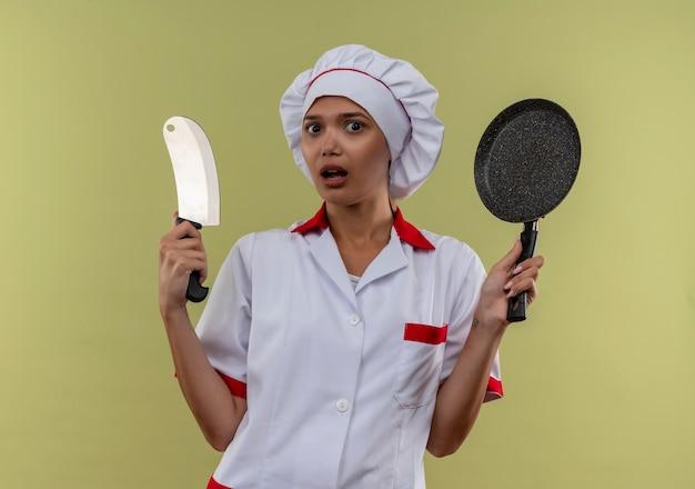 フライパンと包丁を持ったシェフの制服を着た驚いた若い料理人の女性