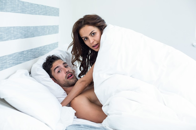 Surprised young couple enjoying on bed