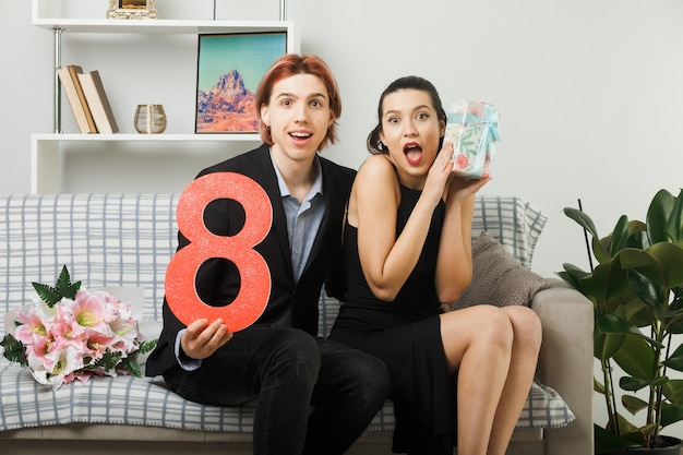 Surprised young couple on happy women day holding number eight with present sitting on sofa in living room
