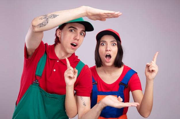 白い壁に隔離された上向きのサイズのジェスチャーの女の子をしているカメラの男を見て建設労働者の制服とキャップで驚いた若いカップル