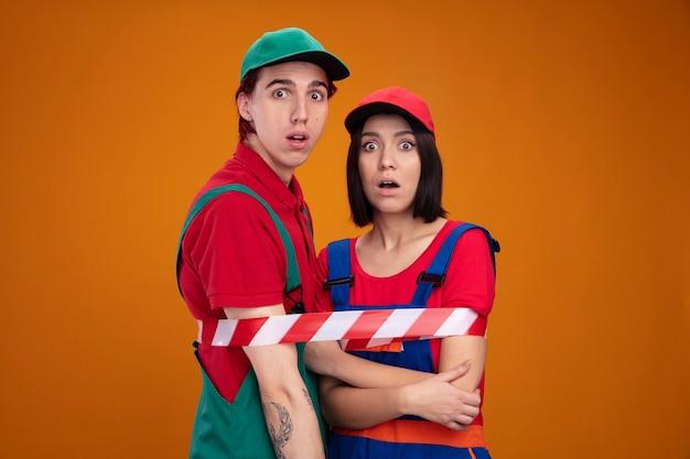 건설 노동자 유니폼을 입고 모자를 쓴 놀란 젊은 부부는 안전 테이프로 묶인 카메라 소녀가 복사 공간이 있는 주황색 벽에 격리된 팔에 손을 얹고 있는 것을 보고 있다