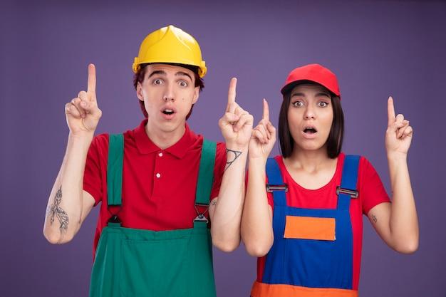 紫色の壁に隔離されたカメラを上向きに見ているキャップを身に着けている安全ヘルメットの女の子を身に着けている建設労働者の制服の男に驚いた若いカップル