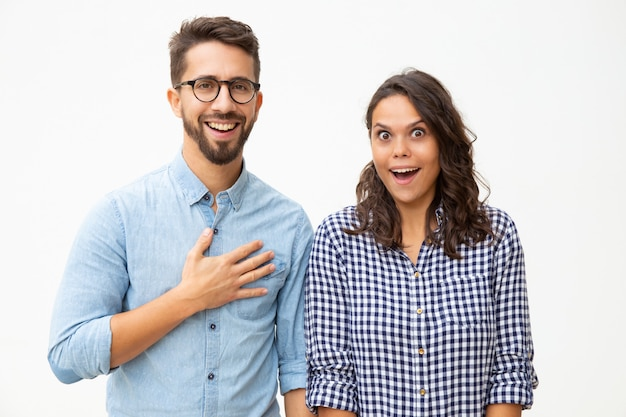 Surprised young couple looking at camera