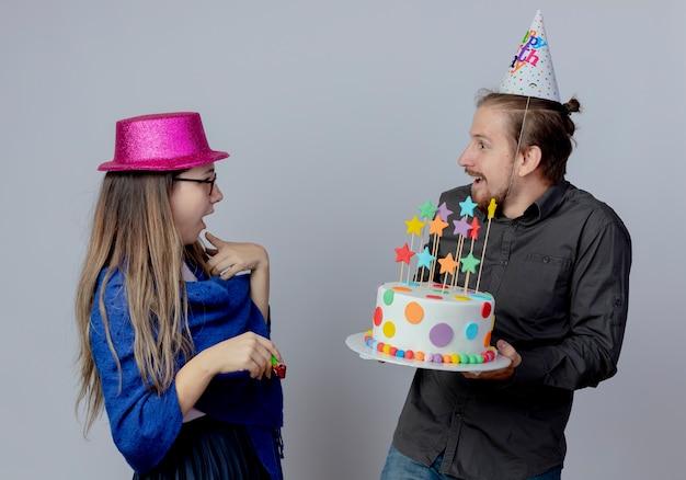 La giovane coppia sorpresa guarda a vicenda la ragazza con gli occhiali che porta il cappello rosa tiene il fischio e l'uomo bello nella torta della tenuta del cappuccio di compleanno isolata sulla parete bianca