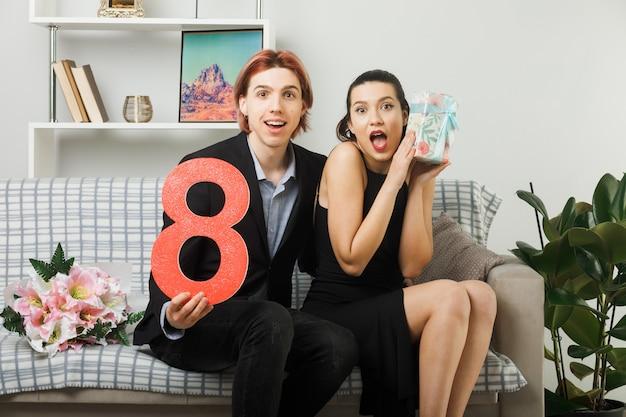 Удивленная молодая пара в счастливый женский день держит номер восемь с подарком, сидя на диване в гостиной