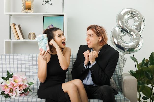 Удивленная молодая пара в день счастливой женщины, держащая настоящего парня, показывающего жест `` да '', сидя на диване в гостиной