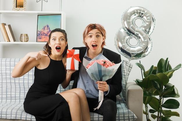 Удивленная молодая пара в счастливый женский день держит подарок с букетом, сидя на диване в гостиной