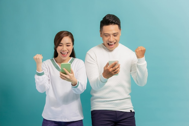 Surprised young couple stand isolated on blue hold smartphones happy win online lottery