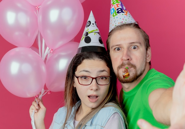 파티 모자를 쓰고 놀란 젊은 부부는 헬륨 풍선을 들고 소녀와 분홍색 벽에 고립 된 휘파람을 불고 남자를 찾습니다