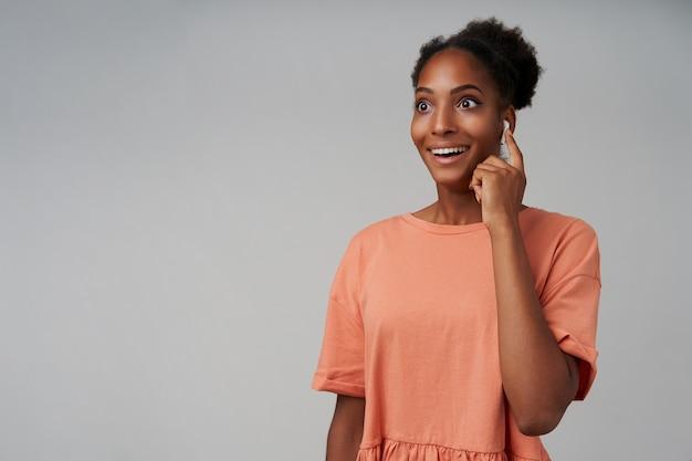 Giovane donna castana riccia sorpresa con pelle scura mantenendo la mano alzata sul suo auricolare mentre guarda con gioia da parte con un ampio sorriso, isolato su grigio