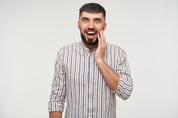 Giovane uomo barbuto dai capelli scuri sorpreso in camicia a righe che tiene il palmo sollevato sulla guancia e guardando con gli occhi spalancati e la bocca aperta, isolato sopra il muro bianco