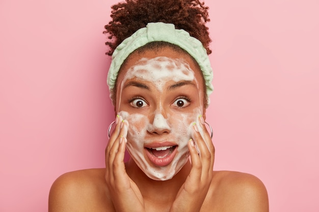 Surprised young dark skinned woman clears face with foam, shocked to be short of time, massages cheeks, concentrated, wears headband, stands with naked body against pink wall