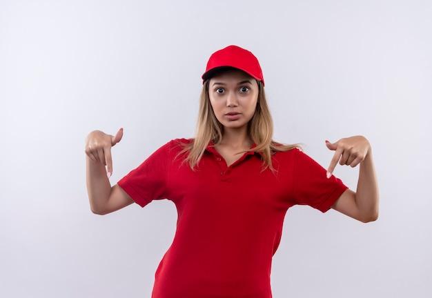 赤い制服とキャップを身に着けている驚いた若い配達の女の子は、白で隔離されたダウンを指します