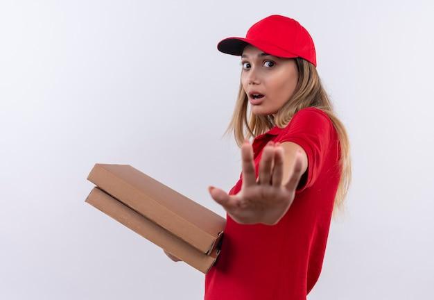 Giovane ragazza sorpresa delle consegne che indossa l'uniforme rossa e il cappuccio che tiene le scatole per pizza e che mostra il gesto di arresto isolato su bianco
