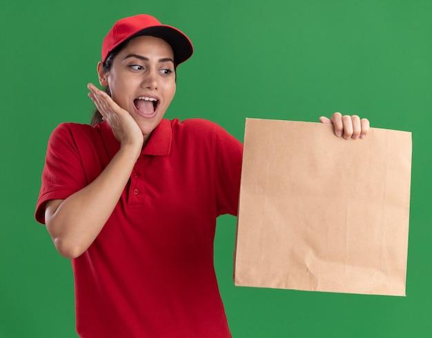 緑の壁に隔離された頬に手を置いて、紙の食品パッケージを保持し、見て制服と帽子を身に着けている驚いた若い配達の女の子