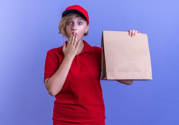 青い壁に隔離された手で制服とキャップを保持している紙の食品バッグで覆われた口を身に着けている驚いた若い配達の女の子