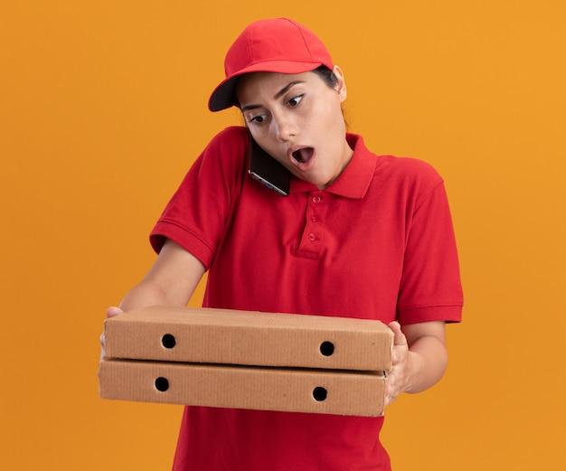Удивленная молодая доставщица в униформе и кепке держит коробки для пиццы и разговаривает по телефону, изолированному на оранжевой стене