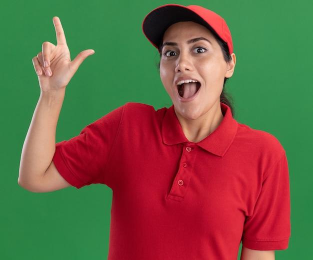 녹색 벽에 고립 된 최대 유니폼과 모자 포인트를 입고 놀란 젊은 배달 소녀